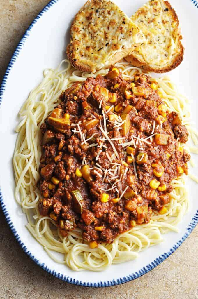 Pasta sauce with zucchini and corn on top of linguini