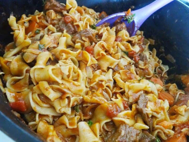 Making goulash in Dutch oven pot with noodles