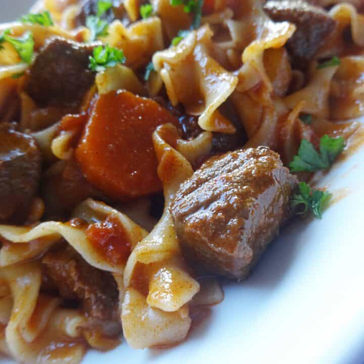 Beef goulash with egg noodles and veggies on plate