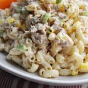 Pasta salad with corn and tuna on white plate